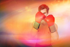 Composite image of muscly man wearing red boxing gloves in guard position Royalty Free Stock Photos
