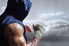 Composite image of muscular man in blue hood with fighting stance Royalty Free Stock Photo