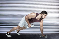Composite image of muscular man doing push ups with dumbbells Royalty Free Stock Photo