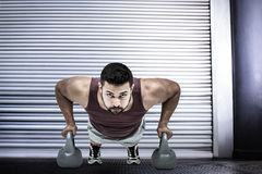 Composite image of muscular man doing push ups with kettlebells Stock Photos