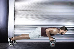 Composite image of muscular man doing push ups with kettlebells Royalty Free Stock Photos