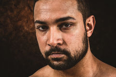 Composite image of muscular man frowning at camera. Muscular man frowning at camera  against dark background Stock Photos