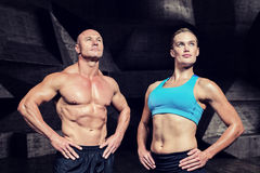 Composite image of muscular man and woman with hand on hip Stock Images