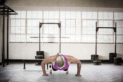 Composite image of muscular woman doing push ups Stock Photo