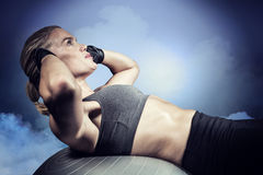 Composite image of muscular woman doing sit ups Stock Images