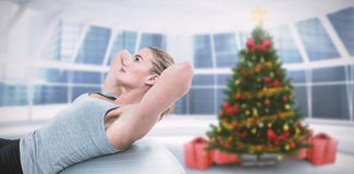 Composite image of muscular woman doing sit ups on exercise ball Royalty Free Stock Image