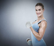 Composite image of muscular woman exercising with dumbbells Royalty Free Stock Image