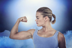Composite image of muscular woman flexing her muscle Stock Image