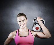 Composite image of muscular woman lifting heavy kettle bell Stock Photos