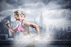 Composite image of muscular woman running in sportswear Royalty Free Stock Image