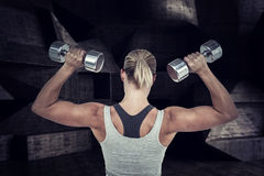Composite image of  muscular woman working out with dumbbells Royalty Free Stock Photo