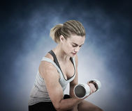 Composite image of  muscular woman working out with dumbbells Stock Photos