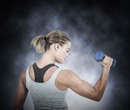 Composite image of  muscular woman working out with dumbbells Royalty Free Stock Images