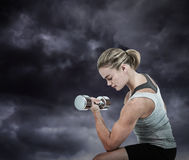 Composite image of muscular woman working out with dumbbells stock images