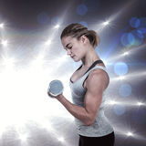 Composite image of  muscular woman working out with dumbbells Royalty Free Stock Photography