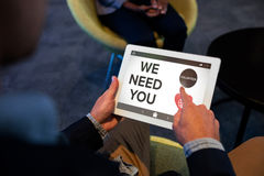 Composite image of we need you text with icons on screen. We Need You text with icons on screen against businessman using digital tablet Royalty Free Stock Photo