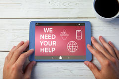 Composite image of we need your help text with various icons on screen. We Need your Help text with various icons on screen against hands using tablet on desk Stock Photos