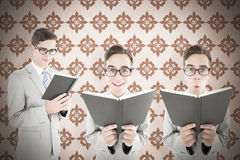 Composite image of nerd reading book. Nerd reading book against background Royalty Free Stock Photography