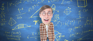 Composite image of nerd smiling. Nerd smiling against blue chalkboard Royalty Free Stock Photo