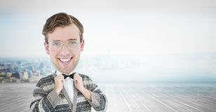 Composite image of nerd smiling. Nerd smiling against city scene in a room Royalty Free Stock Photo