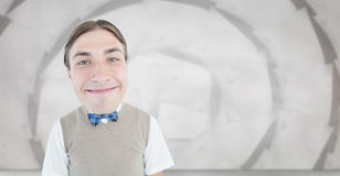 Composite image of nerd smiling. Nerd smiling against sheet spiral on grey wall Stock Photography