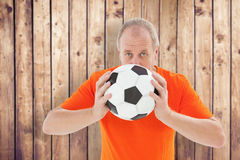 Composite image of nervous football fan holding ball Stock Photography
