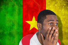 Composite image of nervous football fan looking ahead. Nervous football fan looking ahead against cameroon flag in grunge effect Stock Photography