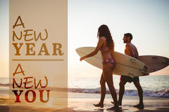 Composite image of new year new you. New year new you against side view of couple holding surfboards while walking stock images