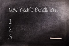 Composite image of new years resolution list. New years resolution list against blackboard with chalk Royalty Free Stock Image