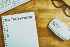 Composite image of new years resolution list. New years resolution list against overhead of notebook and glasses royalty free illustration