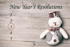 Composite image of new years resolution list. And snowman against wooden wall stock photography