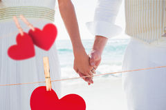Composite image of newlyweds holding hands Royalty Free Stock Photo