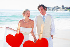 Composite image of newlyweds walking hand in hand and laughing Stock Images