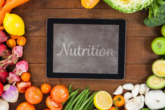 Composite image of nutrition. Nutrition against digital tablet surrounded with fresh vegetables royalty free illustration