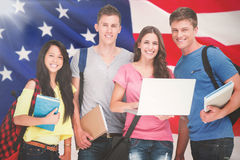 Composite Image Of A Smiling Group Of Students Holding A Laptop While Looking At The Camera Stock Images