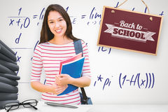 Composite Image Of College Girl Holding Books With Blurred Students In Park Stock Photography