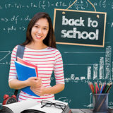 Composite Image Of College Girl Holding Books With Blurred Students In Park Royalty Free Stock Photo