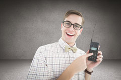 Composite Image Of Geeky Hipster Holding A Retro Cellphone Royalty Free Stock Image