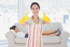 Composite Image Of Happy Woman Giving Thumbs Up In Rubber Gloves Royalty Free Stock Images