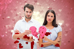 Composite Image Of Upset Couple Holding Two Halves Of Broken Heart Stock Image