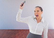Composite image of offended businesswoman screaming and throwing her mobile phone Stock Image