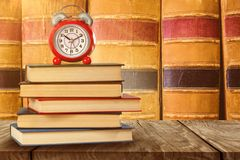 Composite image of old alarm clock and stack of books stock photo