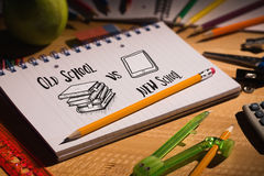 Composite image of old school vs new school doodle. Old school vs new school doodle against students table with school supplies royalty free stock photo