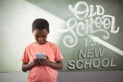 Composite image of old school vs new school. Old school vs new school against boy using cellphone against greenboard in school stock photos