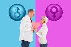 Composite image of older affectionate couple holding pink heart shape Royalty Free Stock Image