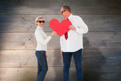 Composite image of older affectionate couple holding red heart shape Royalty Free Stock Photos