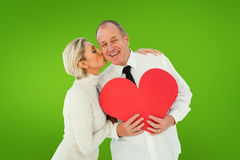 Composite image of older affectionate couple holding red heart shape Stock Image