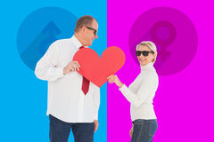 Composite image of older affectionate couple holding red heart shape Stock Photography