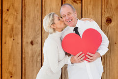 Composite image of older affectionate couple holding red heart shape Stock Photo