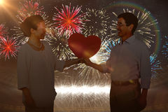 Composite image of older asian couple holding heart. Older asian couple holding heart against fireworks exploding over football stadium Stock Images